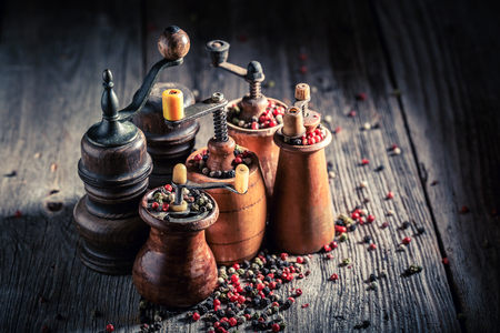 Rustic pepper mills with black and red pepper Stock Photo