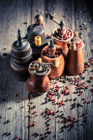 Rustic pepper mills with different types of pepper