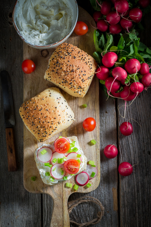 Sandwich with radish, creamy cheese and tomatoes on old table