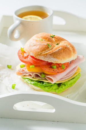 Sandwich with tomatoes, cheesem, ham and tea on white table