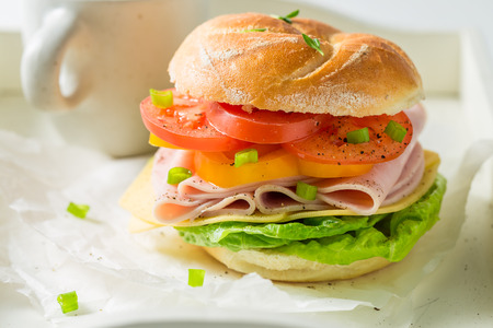 Crisp sandwich with fresh ingredients and tea on white table