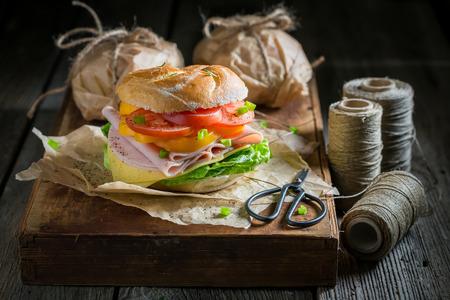 Take away sandwich packed in gray paper in dark mood 写真素材