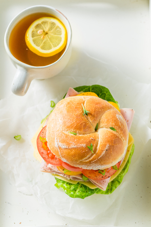 Sandwich with fresh ingredients and hot tea on white table