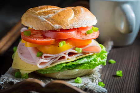 Tasty sandwich with fresh ingredients on wooden table
