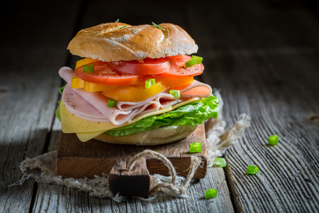 Sandwich with tomatoes, cheese and ham on wooden table