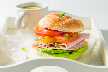 Tasty sandwich with cheese, ham and tea on white table