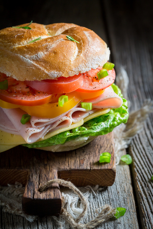 Closeup of big sandwich with tomatoes, cheese and ham