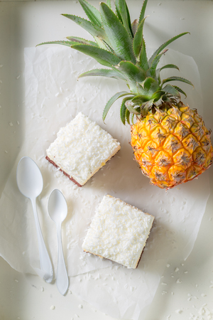 Top view of sweet white cake with pineapple and coconut