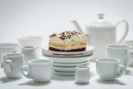 Closeup of sweet white cake with mousse, chocolate and porcelain Stock Photo