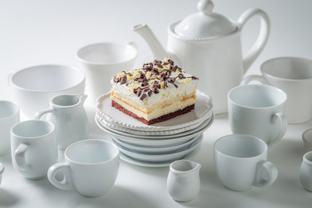 White cake with mousse, chocolate and porcelain on white background