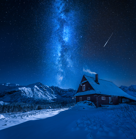 Milky way over mountain cottage in winter, Tatras, Poland