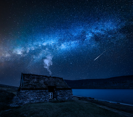 Milky way over cottage with grass on the roof, Iceland