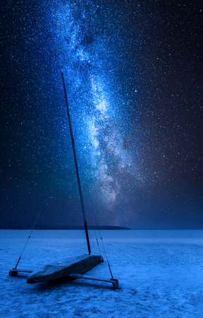 Milky way over ice boat on frozen lake at night Stock fotó