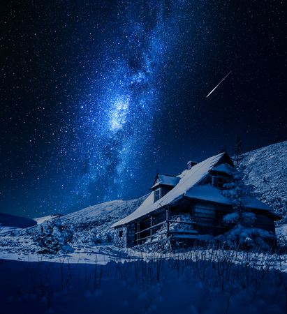 Milky way over wooden mountain cottage in winter, Poland Stockfoto