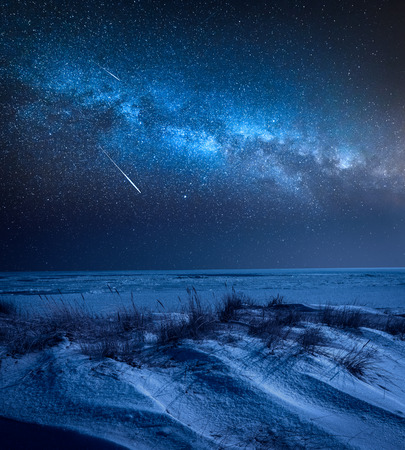 Milky way over frozen beach in winter at night Stock Photo