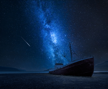 Milchstraße über einem Schiffswrack am Ufer in Island Standard-Bild