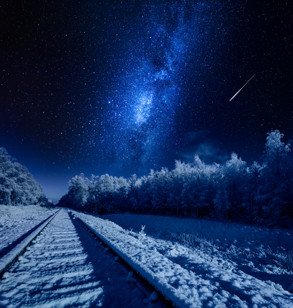 Vía Láctea sobre la línea de ferrocarril congelada en invierno por la noche