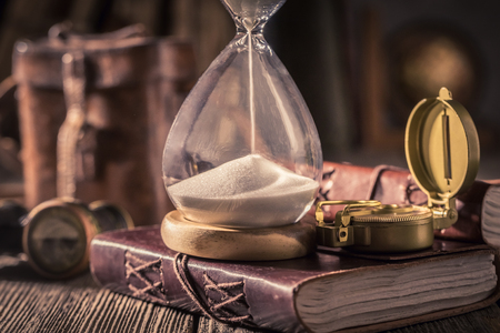 Old hourglass and journal as a concept of travel memories