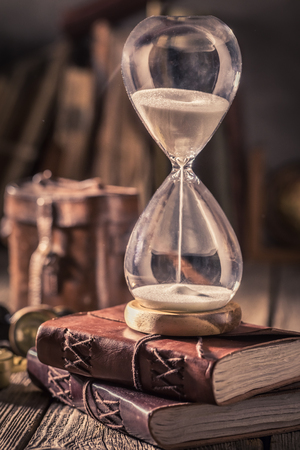 Aged hourglass and journal as a concept of travel memories