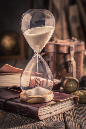 Aged hourglass and journal as a concept of journey diary