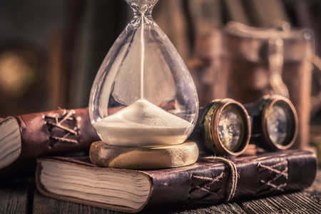 Aged hourglass and journal with binocular and compass