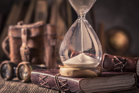 Old hourglass and journal with compass and binocular Banco de Imagens