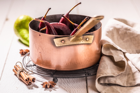Mulled wine with pears and cinnamon on white table Stock Photo