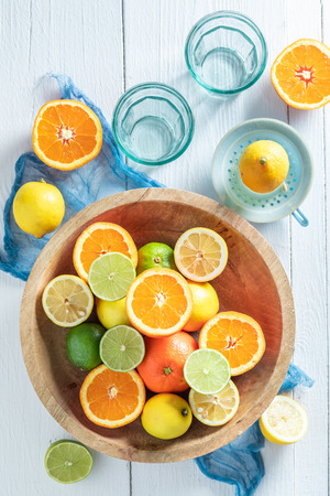 Tasty oranges, limes and lemons with on wooden table