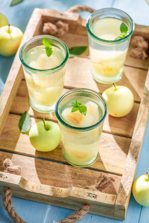 Delicious apple juice on blue wooden table