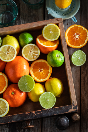 Healthy oranges, limes and lemons with on rustic table
