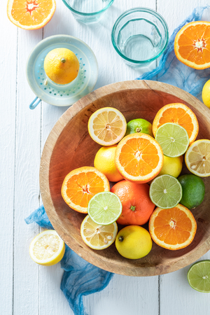 Sweet oranges, limes and lemons with on wooden table