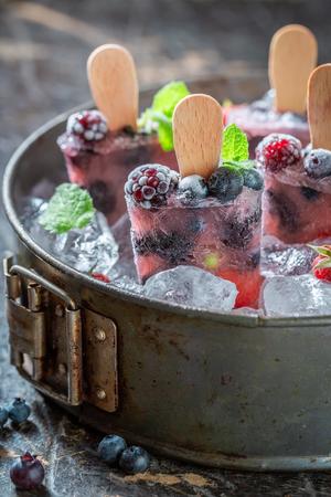 Tasty ice cream with berries on cold ice