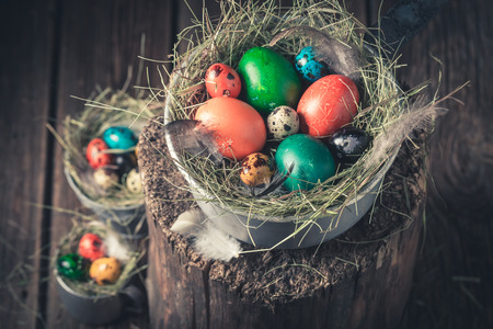 Colourfull eggs for Easter with hay in wooden cottage Stock Photo