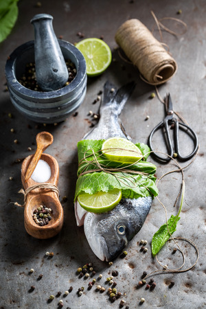 Preparing sea bream with horseradish and lemon on metal table Stock Photo
