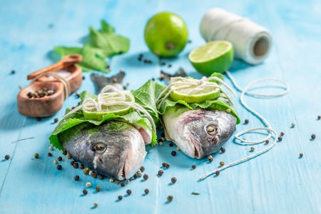 Preparing sea bream with salt and pepper on blue table