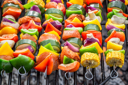 Homemade skewers on grill with vegetables and meat