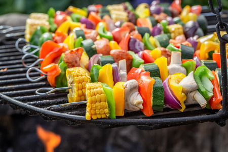 Tasty skewers on grill with vegetables and meat