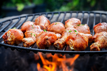 Closeup of chicken leg with herbs on grill
