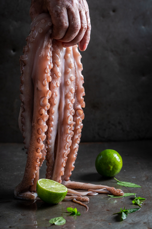 Closeup of freshly caught octopus holding in hand and lime
