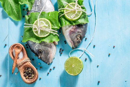 Seasoning whole fish with lime on blue table