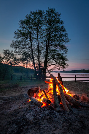 Warm bonfire at dusk by the lake, summer in Poland