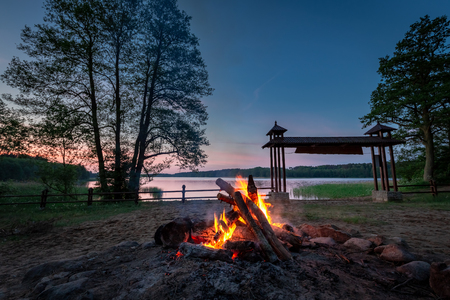 Bonfire at dusk by the lake, summer in Poland