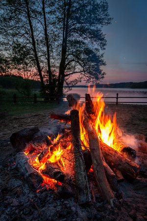 Stunning bonfire at dusk by the lake, summer in Poland