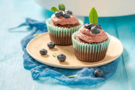 Muffin with blueberries and chocolate cream on blue table Фото со стока