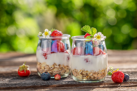Tasty oat flakes in jar with yoghurt and berries