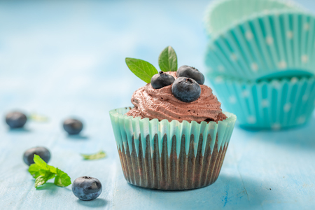 Fresh muffin with blueberries and chocolate cream Фото со стока