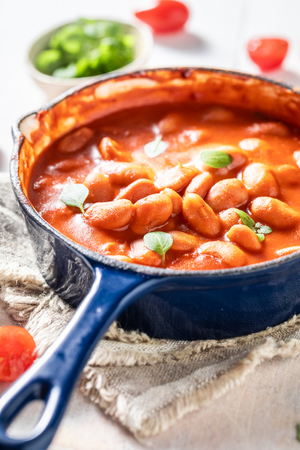 Tasty baked beans with tomato sauce and fresh herbs