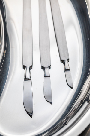 Sharp surgical scalpels on stainless steel table with blood Stock Photo