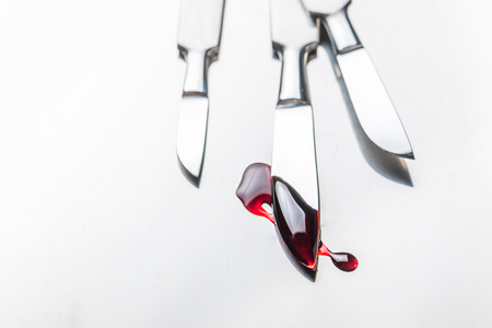 Surgical steel scalpels with blood on stainless steel table
