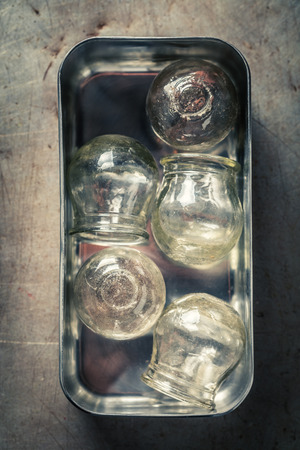 Retro medical cupping glass in a stainless steel container Reklamní fotografie - 119870949